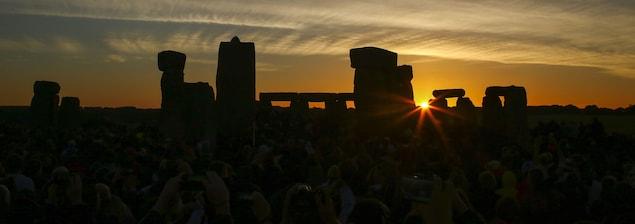 Des gens photographient le soleil qui se lève sur le site Stonehenge.