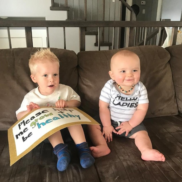 Luke Germs, 3 ans, prend la pose près d'un bébé de 7 mois. Ils sont de la même taille. Luke tient une affiche où il est écrit: «svp, aidez-moi à grandir en santé».
