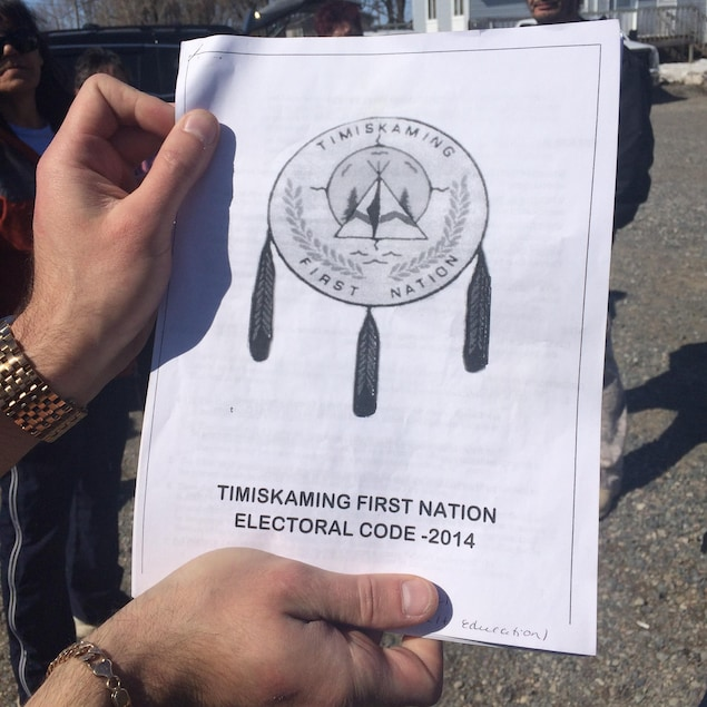 Un homme tient le code électoral de la Timiskaming First Nation, datant de 2014.