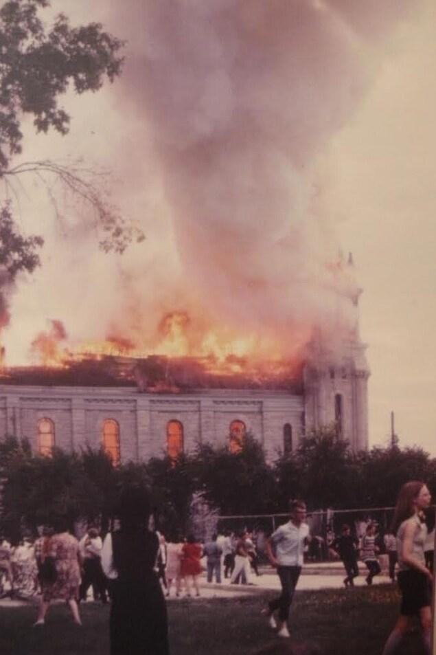 Un tourbillon infernal de flammes dévore le toit d'une cathédrale, une foule fuit le feu.