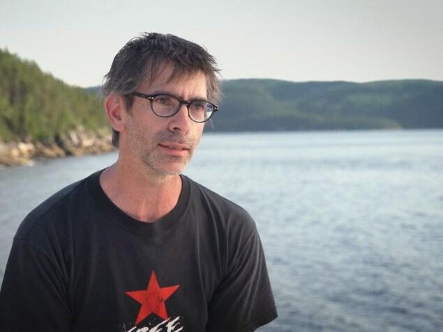 On voit M. Bourgault, de face, qui parle à la caméra. En arrière-plan, on voit le fjord du Saguenay.