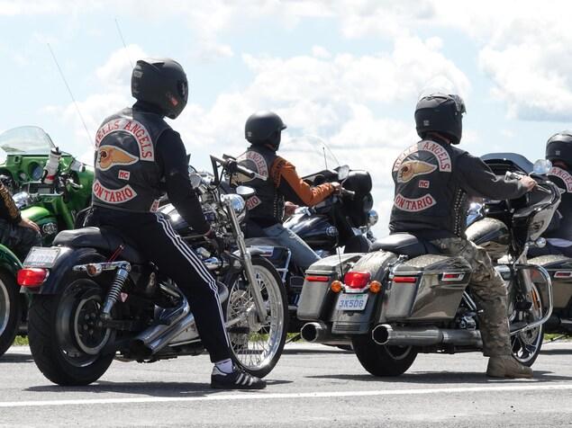 Des membres des Hells Angles attendent sur leur moto en file sur la route.