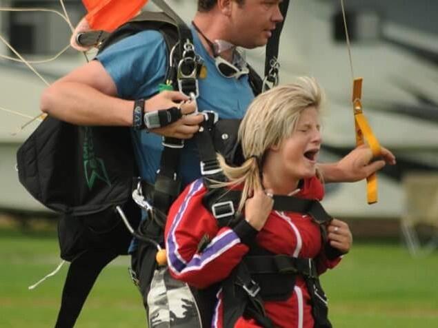 Karine Duval avec l'équipement pour un saut en parachute, avec un instructeur.