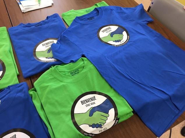 Des t-shirts placés sur une table arborent le slogan «bienvenue chez vous» et le logo du comité d'accueil des nouveaux arrivants de Val-d'Or.