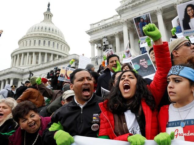 Des manifestants crient et brandissent des pancartes devant le Capitole.