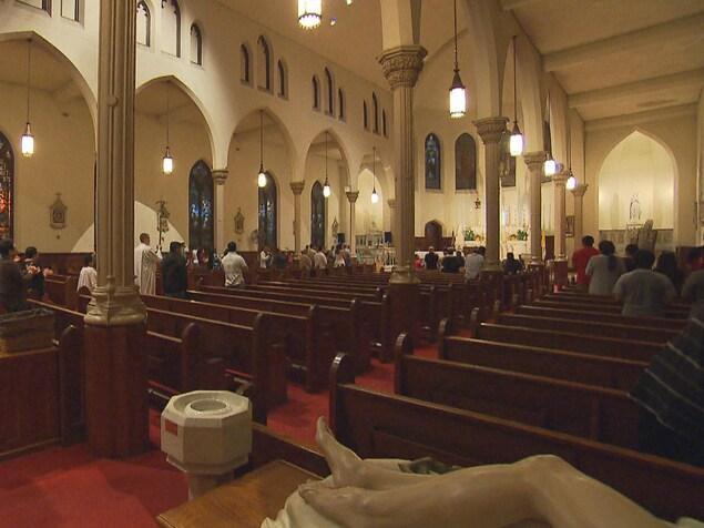 Des personnes se tiennent debout dans une église, alors qu'il semble faire sombre à l'extérieur. Elles sont peu nombreuses.