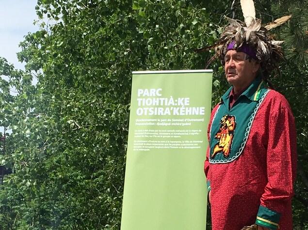 Un Autochtone vêtu d'habits traditionnels, comme une petite coiffe de plume, se tient devant une affiche montrant le nouveau nom du parc au sommet d'Outremont.
