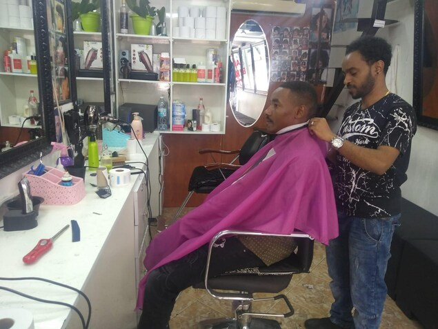 Le barbier est en train de s'occuper de son client.