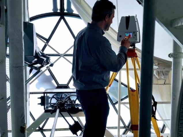 On voit un homme, de dos, qui manipule un appareil servant à scanner les éléments d'architecture. Devant lui se trouve les mécanismes de l'horloge du parlement.