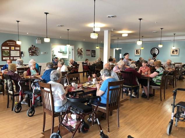 Des personnes âgées, assises autour de plusieurs tables, sont en train de manger.