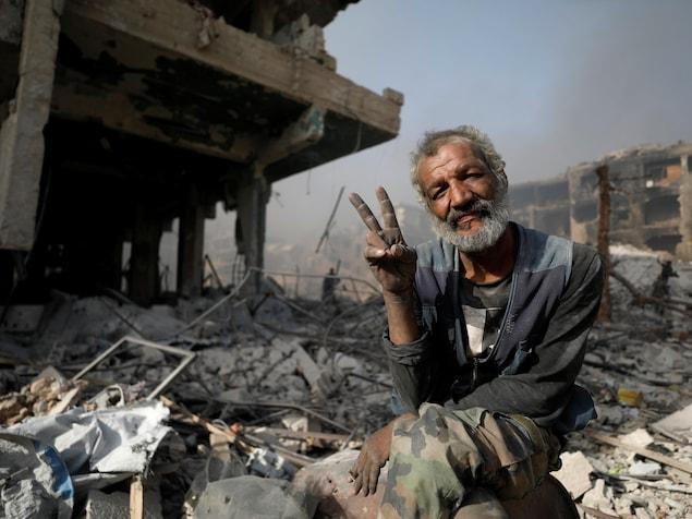 Un homme se tient au milieu des ruines de la ville de Damas.