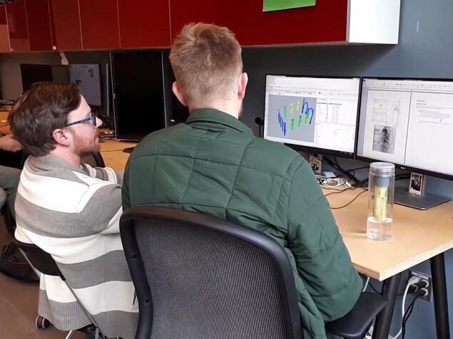 On voit deux étudiants, de dos, devant un ordinateur montrant une modélisation 3D d'une élément architectural.