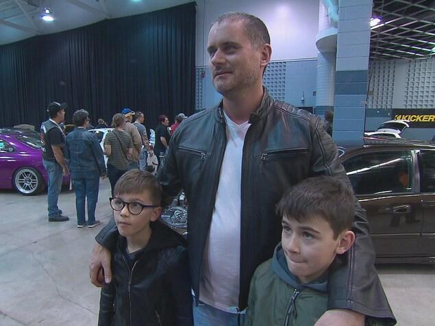 Un père avec ses deux fils dans un salon d'automobiles modifiées.