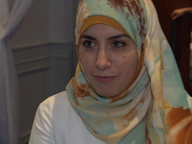 Une jeune femme musulmane portant un voile regarde un journaliste lors d'une entrevue.