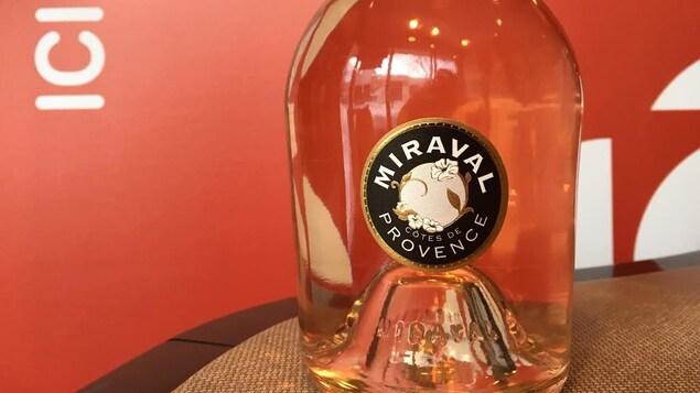 Une bouteille de vin rosé dans un studio radio devant une affiche de Radio-Canada