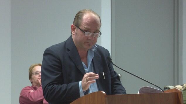 Au lutrin de la salle du conseil municipal de Nipissing Ouest, Dany H. Poulin s'adresse aux élus.