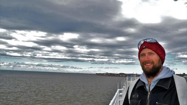 Éros D'Astous pose devant le fleuve Saint-Laurent le regard confiant