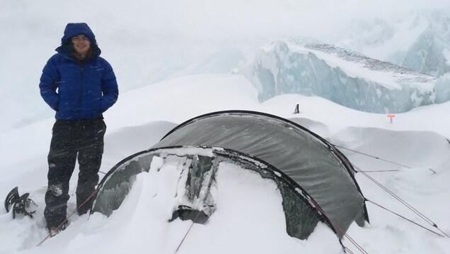 Jean-François est debout à côté de sa tente dans une tempête de neige.
