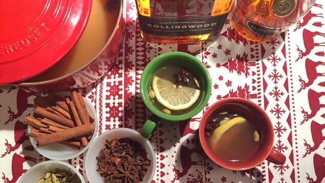 Une casserole de cidre chaud avec des bouteilles de spiritueux, des épices et deux tasses.