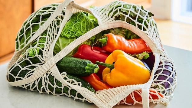 Des légumes frais dans un sac réutilisable en coton, dans une cuisine lumineuse.