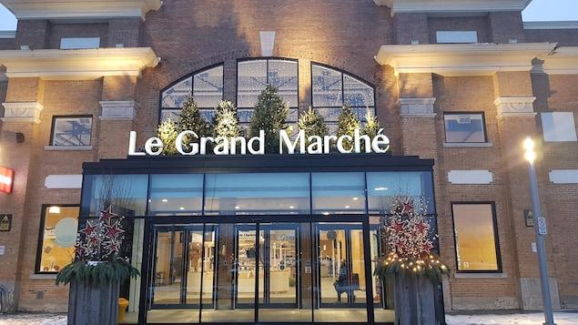 Entrée vitrée moderne sur une façade en briques avec l'inscription Le Grande Marché.