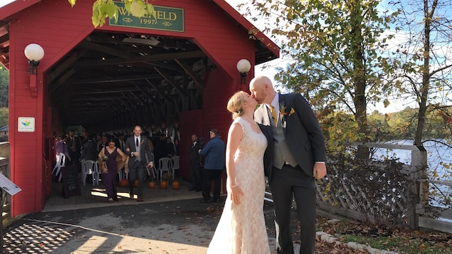 Un couple s'embrasse devant l'entrée du pont couvert Gendron à Wakefield. Derrière, des invités sortent du pont où a eu lieu la cérémonie de mariage.