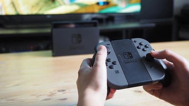 Une personne tient dans ses mains les manettes d'une console de jeux Nintendo Switch.