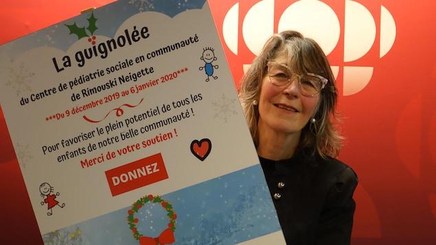 Odette Lefebvre, une femme avec des lunette et une pancarte arborant la guignolée du centre pédiatrique