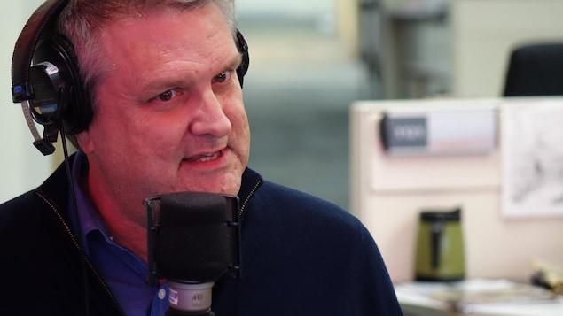 Peter Galbraith, un casque audio sur les oreilles devant le micro de la radio.