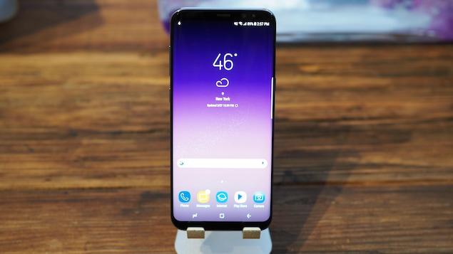 Un téléphone intelligent de la marque Samsung sur un support sur un comptoir en bois.