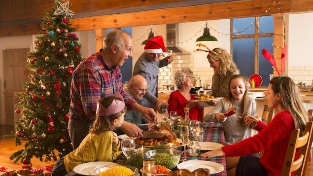 Une famille est assise autour d'une table. Il y a un sapin de Noël.