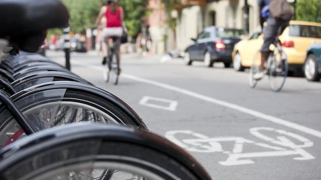 Des vélo Bixi stationné dans une rue avec des cyclistes en floue à l'arrière.