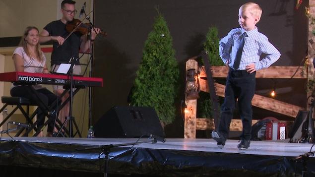 Un jeune garçon vêtu d'une cravate danse la claquettes sur scène aux côté d'une pianiste et d'un violoniste.
