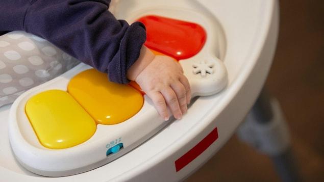 Un bébé dans une chaise sauteuse appuie sa main sur un jouet.