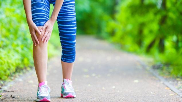 Une femme se tient le genou.