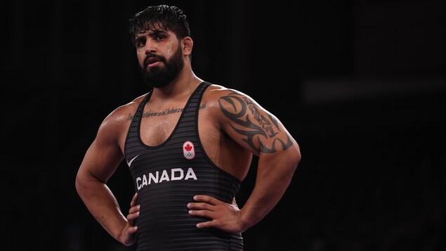 Un lutteur canadien regarde son entraîneur avec les mains sur les hanches.