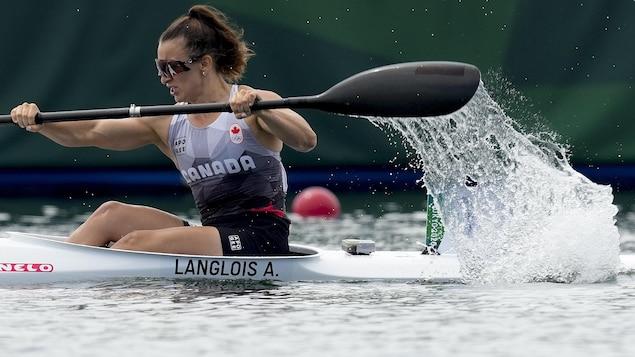 Une femme pagaie dans son kayak.