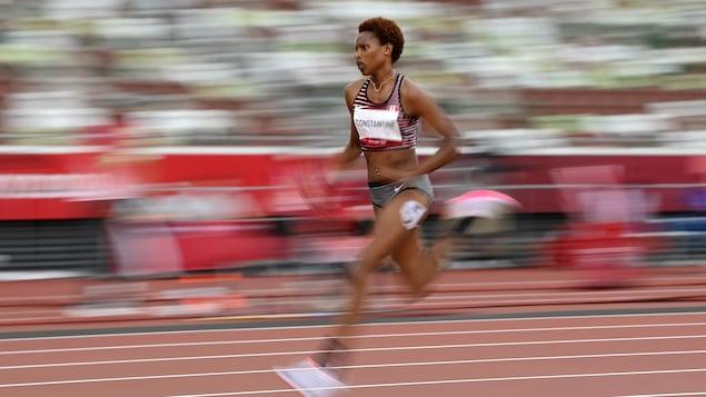 Une athlète court sur la piste d'athlétisme.