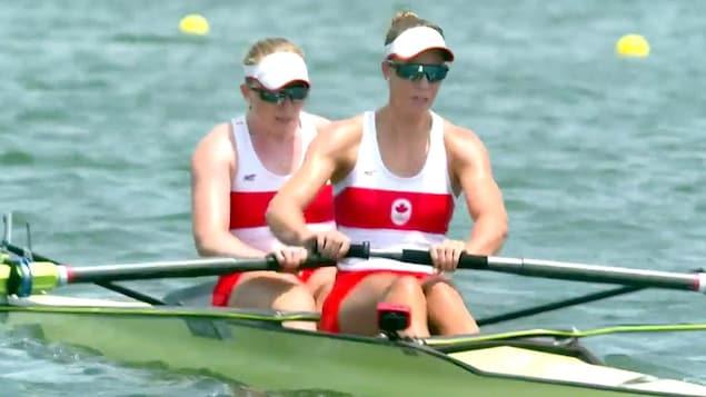 Deux femmes donnent un bon effort avec leur rame pour faire avancer leur aviron.