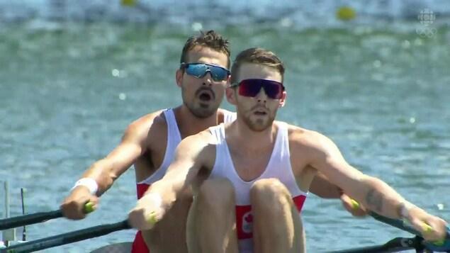Deux hommes rament sur leur canoe. Ils portent des lunettes et donnent un effort physique important.