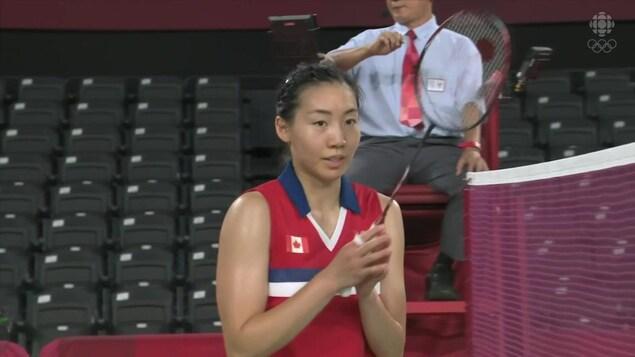 Michelle Li, raquette en main, salue les mains collées suite à sa victoire aux Jeux olympiques de Tokyo.