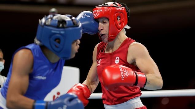 Myriam Da Silva Rondeau qui est en rouge, de l'équipe Canada reçoit un coup de  Maria Altagracia Moronta Hernandez, en bleu, de la République Dominicaine durant le combat des femmes poids 64-69 kg.