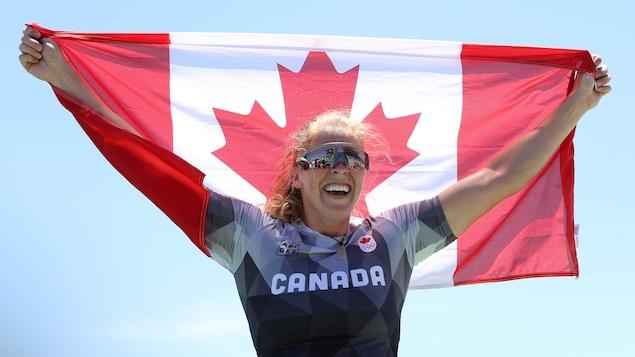 Laurence Vincent-Lapointe tient un drapeau du Canada dans les airs avec un grand sourire.