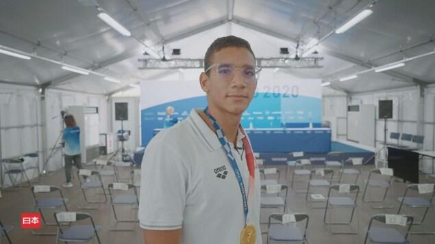L'athlète Ahmed Hafnaoui pose fièrement, la médaille au cou.