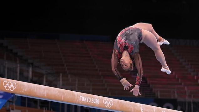 La gymnaste effectue une pirouette arrière.