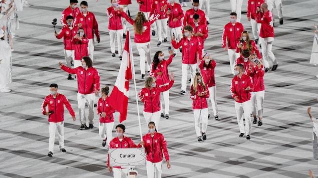 Los abanderados canadienses Miranda Ayim y Nathan Hirayama marchan con la bandera de Canadá. Les sigue la delegación canadiense.