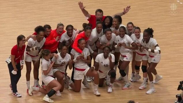 Toutes les joueuses de l'équipe de handball de la France sourient à pleines dents alors qu'elles sont entourées des entraîneurs pour la prise d'une photo d'équipe après leur victoire en grande finale.