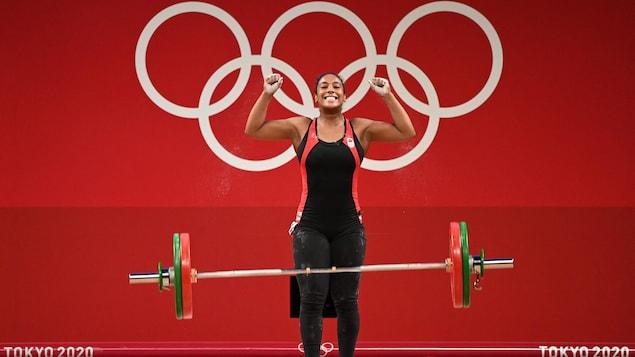 Une jeune femme a les bras dans les airs pour célébrer après avoir levé une charge importante en haltérophilie aux Jeux olympiques.