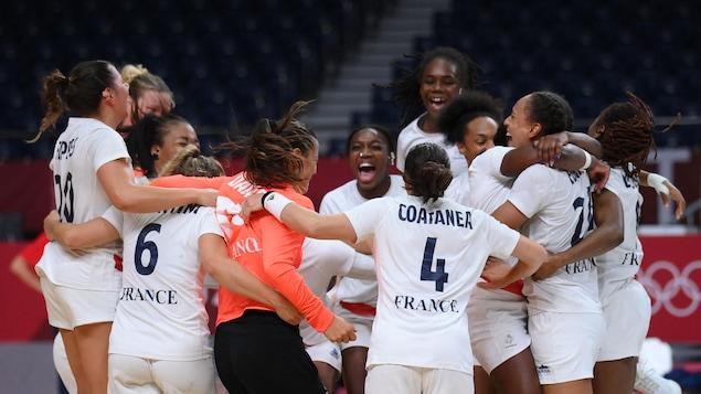 Des joueuses de handball se sautent dans les bras pour célébrer une victoire. Elles portent un uniforme blanc et ont toutes un gros sourire.
