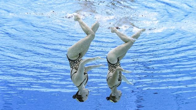 Les deux nageuses artistiques sont sous l'eau, la tête en bas.
